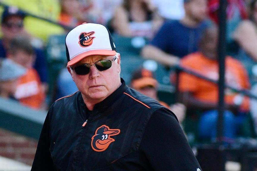 Buck Showalter in Orioles gear with sunglasses on