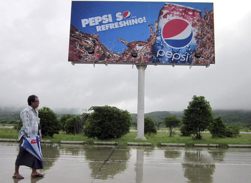 FILE - In this Aug. 11, 2012 file photo, a man walks past a Pepsi advertisement in Naypyitaw, Myanmar. PepsiCo Inc. will start selling its drinks in Myanmar, following the U.S. government's decision to suspend investment sanctions on the country for its democratic reforms. Myanmar's new foreign investment law envisions broad powers for the country's already over-taxed investment commission, restricts foreign investment in 11 poorly defined areas and requires local hiring, according to a copy of the widely misunderstood law obtained by The Associated Press. (AP Photo/Khin Maung Win, File)