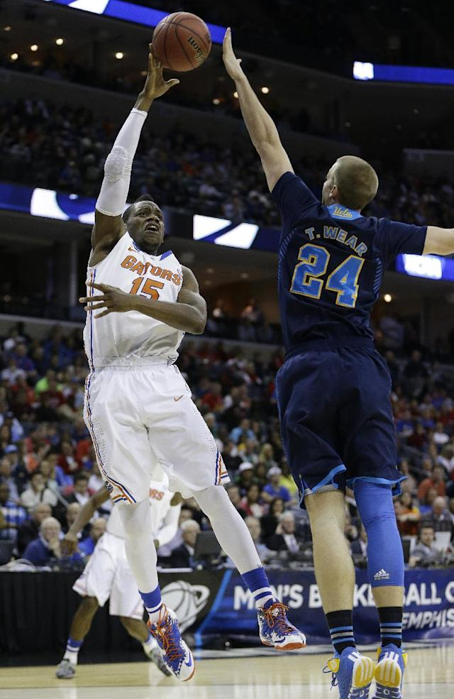 Florida forward Will Yeguete (15) shoots over UCLA forward Travis Wear (24) during the first half in a regional semifinal game at the NCAA college basketball tournament, Thursday, March 27, 2014, in Memphis, Tenn. (AP Photo/Mark Humphrey)