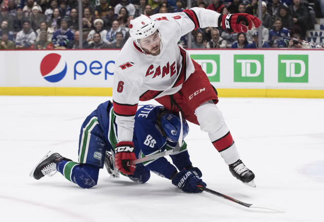 Carolina Hurricanes' Joel Edmundson (6) falls over Vancouver Canucks' Adam Gaudette (88) during the second period of an NHL hockey game in Vancouver, British Columbia, Thursday, Dec. 12, 2019. (Darryl Dyck/The Canadian Press via AP)