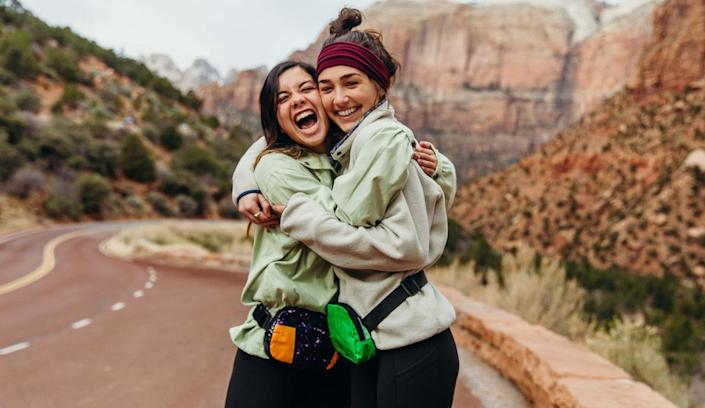 Two young girls beam with joy wearing their upcycled Rareform fanny packs.