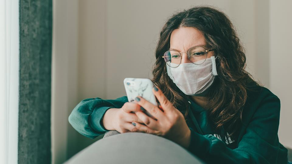 Young woman covering her face with surgical mask and using smartphone to find information about coronavirus spread on internet.