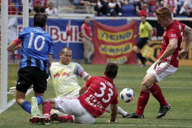 New York Red Bulls goalkeeper Luis Robles, center left, gets helped by midfielder Aaron Long (33) and defender Tim Parker (26) while defending against Montreal Impact midfielder Ignacio Piatti (10) during the first half of a soccer match, Saturday, April 14, 2018, in Harrison, N.J. (AP Photo/Julio Cortez)