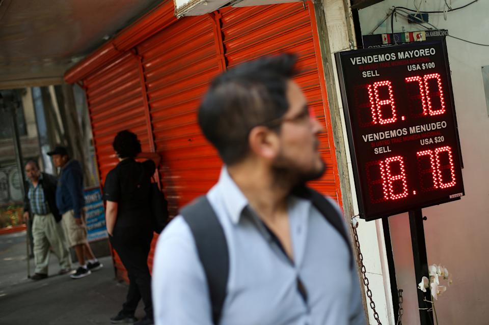 A man walksin front of a board displaying the exchange rate for Mexican Peso and U.S. Dollar at a foreign exchange house in Mexico City, Mexico September 4, 2019. REUTERS/Edgard Garrido