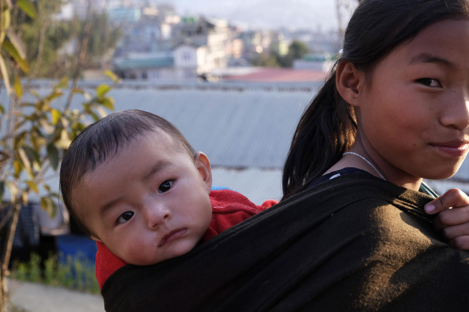 A young Naga girl carrying a child on her back reacts to camera in Kohima, capital of the northeastern Indian state of Nagaland, Sunday, March 1, 2020. Nagaland is home to the indigenous Nagas and borders Myanmar in the east. (AP Photo/Yirmiyan Arthur)