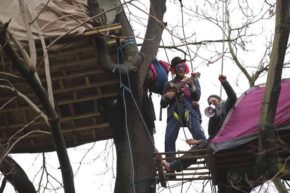 Protesters in trees at the encampment in Euston Square Gardens in central London, Wednesday Jan. 27, 2021. Protesters against a high-speed rail link between London and the north of England said Wednesday that some of them have been evicted from a park in the capital after they dug tunnels and set up a makeshift camp. (Aaron Chown/PA via AP)