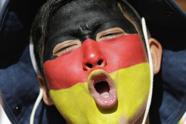 A fan with his face painted with the colors of the German flag cheers before the start of the World Cup final soccer match between Germany and Argentina at Maracana Stadium in Rio de Janeiro, Brazil, Sunday, July 13, 2014. (AP Photo/Victor R. Caivano)