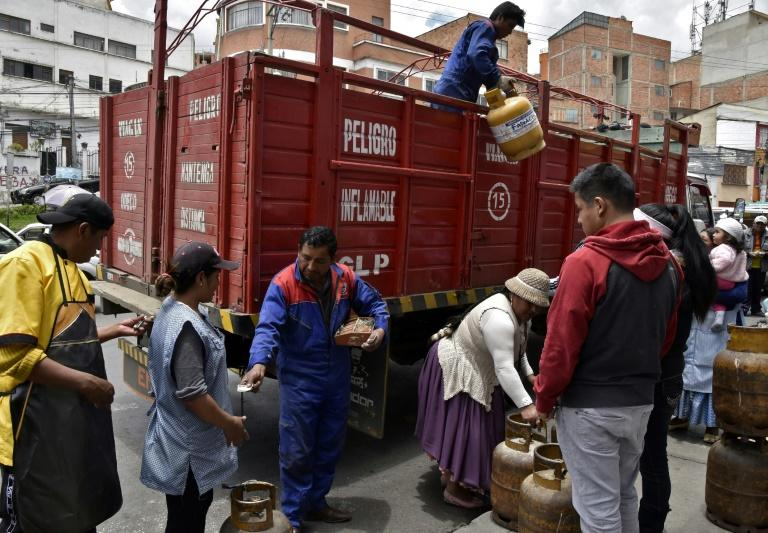 A man downloads gas cylinders from a truck in La Paz as workers return after weeks of protests