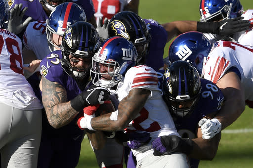 New York Giants running back Wayne Gallman, center, is stopped by Baltimore Ravens defensive end Derek Wolfe (95) and defensive tackle Brandon Williams (98) while running the ball during the first half of an NFL football game, Sunday, Dec. 27, 2020, in Baltimore. (AP Photo/Nick Wass)
