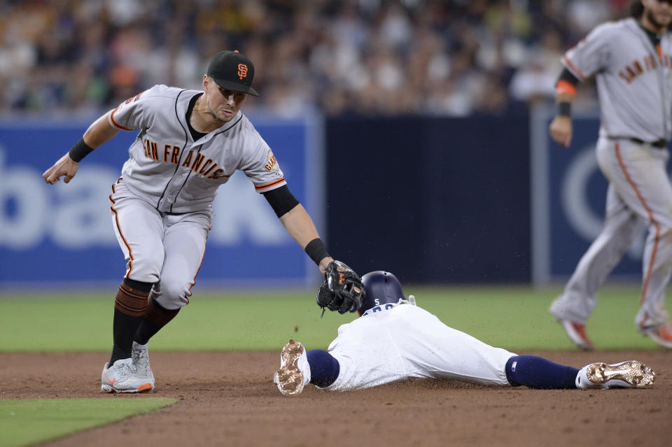 San Diego Padres' Greg Garcia, center, is caught stealing as San Francisco Giants second baseman Joe Panik, left, applies the tag during the sixth inning of a baseball game Saturday, July 27, 2019, in San Diego. (AP Photo/Orlando Ramirez)