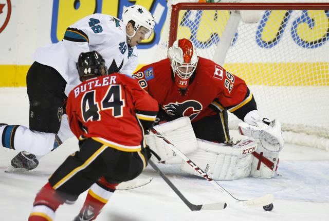 San Jose Sharks' Tomas Hertl, center, from the Czech Republic, tries to get the puck past Calgary Flames goalie Reto Berra, right, from Switzerland, as Chris Butler chases him during the first period of an NHL hockey game Tuesday, Nov. 12, 2013, in Calgary, Alberta. (AP Photo/The Canadian Press, Jeff McIntosh)
