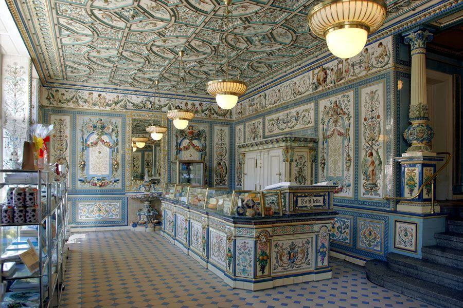 <p>The pink and blue cake shop is both Agatha's employer and the site of the Courtesan au Chocolat, a sweet treat loved by characters in the town of Zubrowka. The interior was shot entirely in a real shop in Dresden, Germany with minor alterations. The original painted frescoes and embossed ceilings really exist in the dairy shop, regularly visited by villagers and tourists alike for milk, cheese, and, strangely, cosmetics. </p>