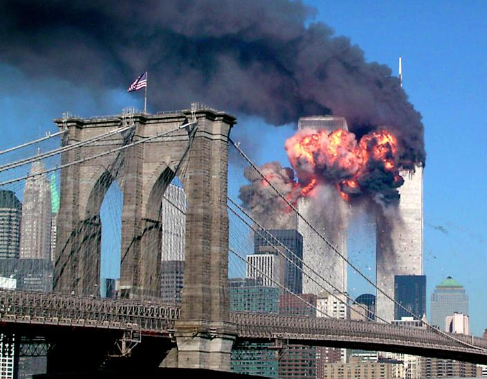 """The South Tower of the World Trade Center explodes in flames after being hit by the hijacked airliner now universally known as """"the second plane,"""" United Airlines Flight 175, September 11, 2001. This photo -- with its black smoke; the shocking, brilliant, colossal flames; the cloudless sky; the beautiful Brooklyn Bridge flying the American flag -- captures so much of the story of the day that, if one were to create a composite picture to illustrate the idea of """"9/11,"""" the result might look very much like this astonishing shot. <br><br>(Photo: STR/Reuters /Landov)<br><br>For the full photo collection, go to <a href=""""http://www.life.com/gallery/59971/911-the-25-most-powerful-photos#index/0"""" rel=""""nofollow noopener"""" target=""""_blank"""" data-ylk=""""slk:LIFE.com"""" class=""""link rapid-noclick-resp"""">LIFE.com</a>"""