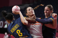 <p>Spain's Lara Gonzalez Ortega, center, challenges for the ball with Sweden's Jamina Roberts, left, and Carin Stromber during the women's Preliminary Round Group B handball match between Spain and Sweden at the 2020 Summer Olympics, Sunday, July 25, 2021, in Tokyo, Japan. (AP Photo/Pavel Golovkin)</p>