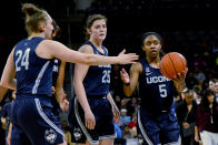 Connecticut guard Anna Makurat (24) celebrates with forward Kyla Irwin (25) and guard Crystal Dangerfield (5) after beating DePaul Blue Demons 84-74 after an NCAA college basketball game on Monday, Dec. 16, 2019. in Chicago, Ill. (AP Photo/Matt Marton)