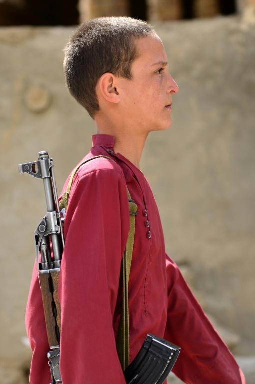 An Afghan youth carrying a rifle walks along a street as resistance forces gather in the Panjshir Valley (AFP/AHMAD SAHEL ARMAN)