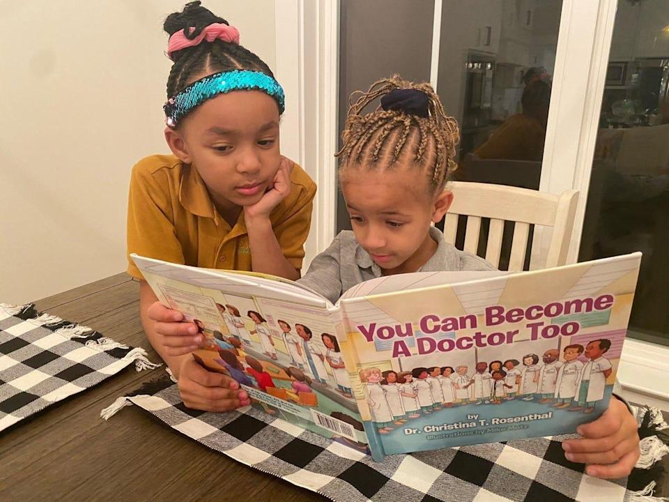 Second grader Skylar Tolbert, 7, peers over the shoulder of her younger sister, Sydney, 6, a kindergartner at Libertas School of Memphis. The sisters read at home each night after school.