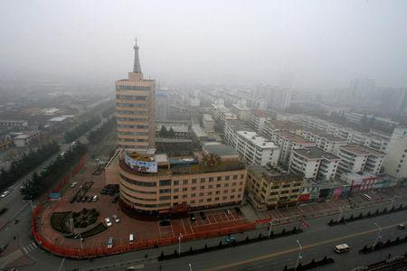 FILE PHOTO: Fog blankets Jincheng City skyline in north China's Shanxi province
