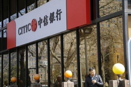 A man stands in front of CITIC bank's branch in Beijing
