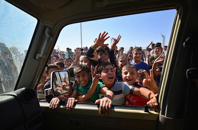 <p>Iraqi boys gather on the road as they welcome Iraqi security forces members, who continue to advance in military vehicles in Kirkuk, Iraq, Oct. 16, 2017. (Photo: Stringer/Reuters) </p>