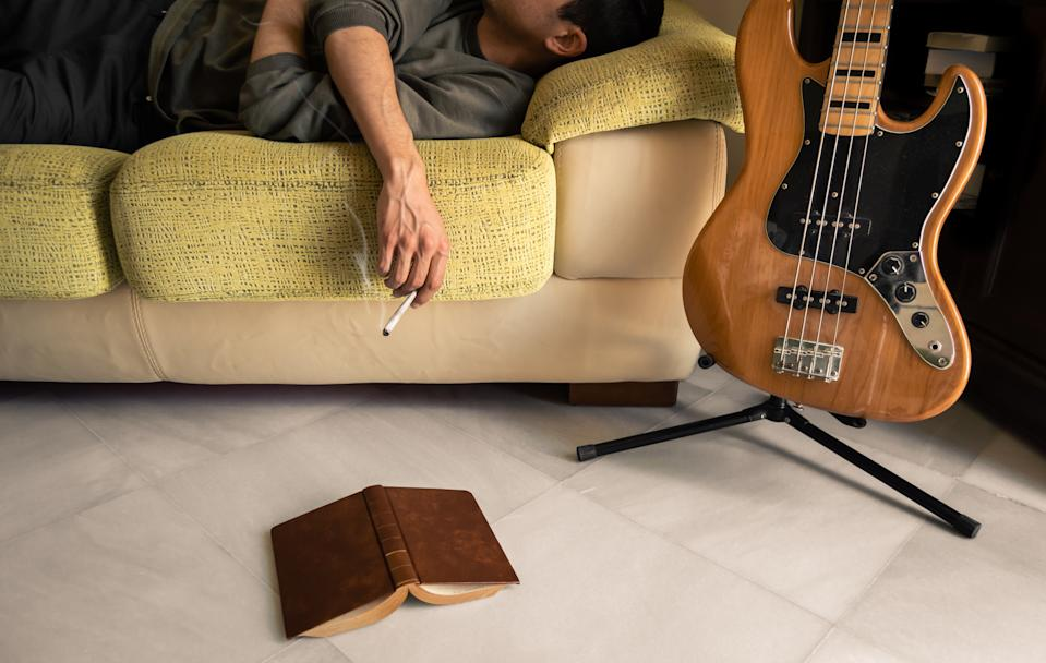 Man smoking marijuana to sleep and relax. Man lying and resting on a sofa smokes a big joint after reading a book and play electric bass.