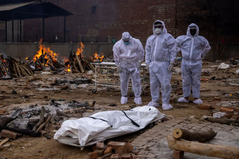 Men wearing protective suits stand next to the body of their relative, who died from the coronavirus disease (COVID-19), before her cremation at a crematorium ground in New Delhi