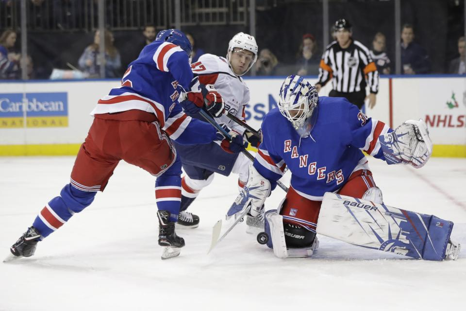 New York Rangers goaltender Henrik Lundqvist, right, stops a shot on goal by Washington Capitals' Beck Malenstyn, center, as Libor Hajek defends during the first period of an NHL hockey game Wednesday, Nov. 20, 2019, in New York. (AP Photo/Frank Franklin II)