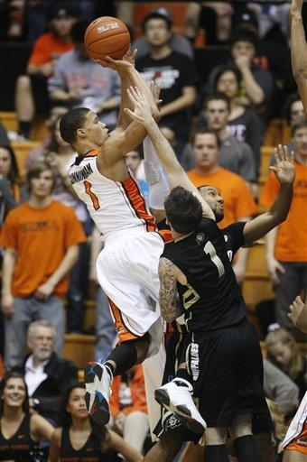 Oregon State's Jared Cunningham (1) shoots as Colorado's Nate Tomlinson (1) and Carlon Brown defends in the first half of an NCAA basketball game Saturday, March 3, 2012, in Corvallis, Ore. (AP Photo/Rick Bowmer)