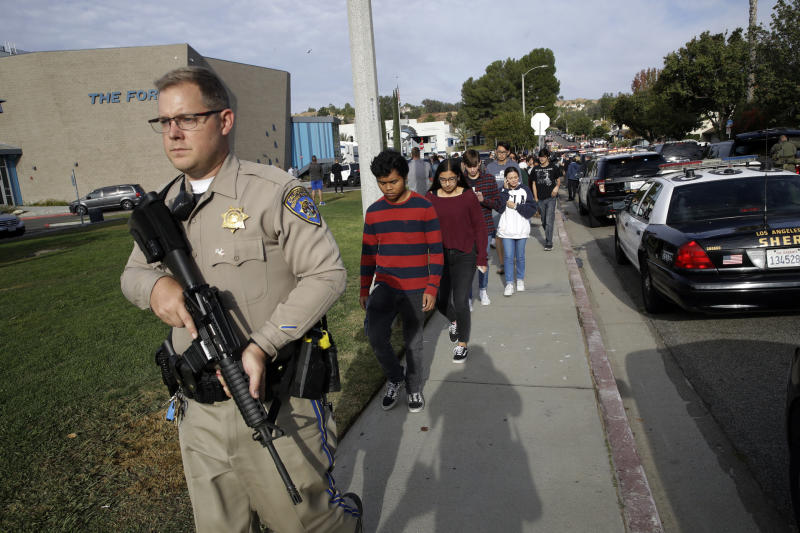 """File-This Nov. 14, 2019, file photo shows students being escorted out of Saugus High School after reports of a shooting in Santa Clarita, Calif. For a few hundred dollars, tools and some elbow grease, you can make your very own rifle or handgun. It's all perfectly legal and it can be done without leaving anything behind for the government to trace. These so-called """"ghost guns"""" have long been popular among hobbyists or gun enthusiasts. But gun-control advocates say they are increasingly popping up in crimes, used by people who are prohibited from buying a firearm and are trying to circumvent a background check.  Authorities said the teenager who fatally shot two classmates and wounded three others before saving the last bullet to kill himself, used a homemade handgun.(AP Photo/Marcio Jose Sanchez, File)"""