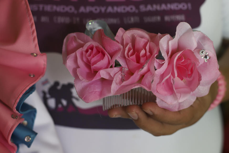 """Venus Nolasco, director of the San Miguel LGBTQ collective """"Pearls of the East,"""" holds a hair side comb that belonged to her friend Zashy Zuley del Cid Velasquez, in San Miguel, El Salvador, Tuesday, May 25, 2021. Rejected by her family, Del Cid fled her coastal village in 2014, the first of a series of forced displacements across El Salvador. She had hoped that in the larger city of San Miguel she could live as a transgender woman without discrimination and violence but there she was threatened by a gang. (AP Photo/Salvador Melendez)"""