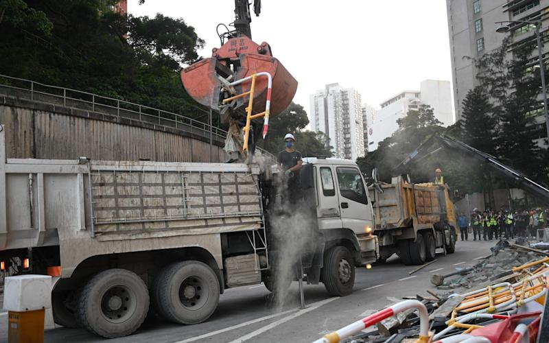 A worker removes debris left by pro-democracy protesters near the Chinese University of Hong Kong (CUHK) on November 16, 2019. - AFP