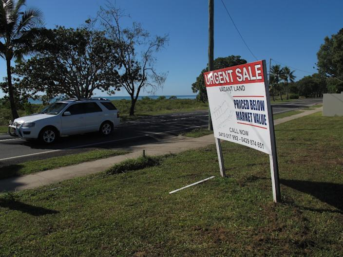 In this photo taken on Friday, June 14, 2013, a car drives past a residential block for sale below market value on the outskirts Mackay city, Queensland state, Australia. A slump in real estate prices is one of the consequences of the fall in coal prices. (AP Photo/Rod McGuirk)