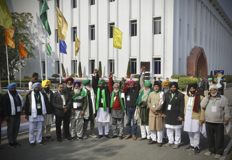 Farmer leaders stand together before going in for a meeting with government representatives in New Delhi, India, Wednesday, Dec. 30, 2020. Protesting farmers fear the government will stop buying grain at minimum guaranteed prices and corporations will then push down prices. The government says the three laws approved by Parliament in September will enable farmers to market their produce and boost production through private investment. (AP Photo/Manish Swarup)