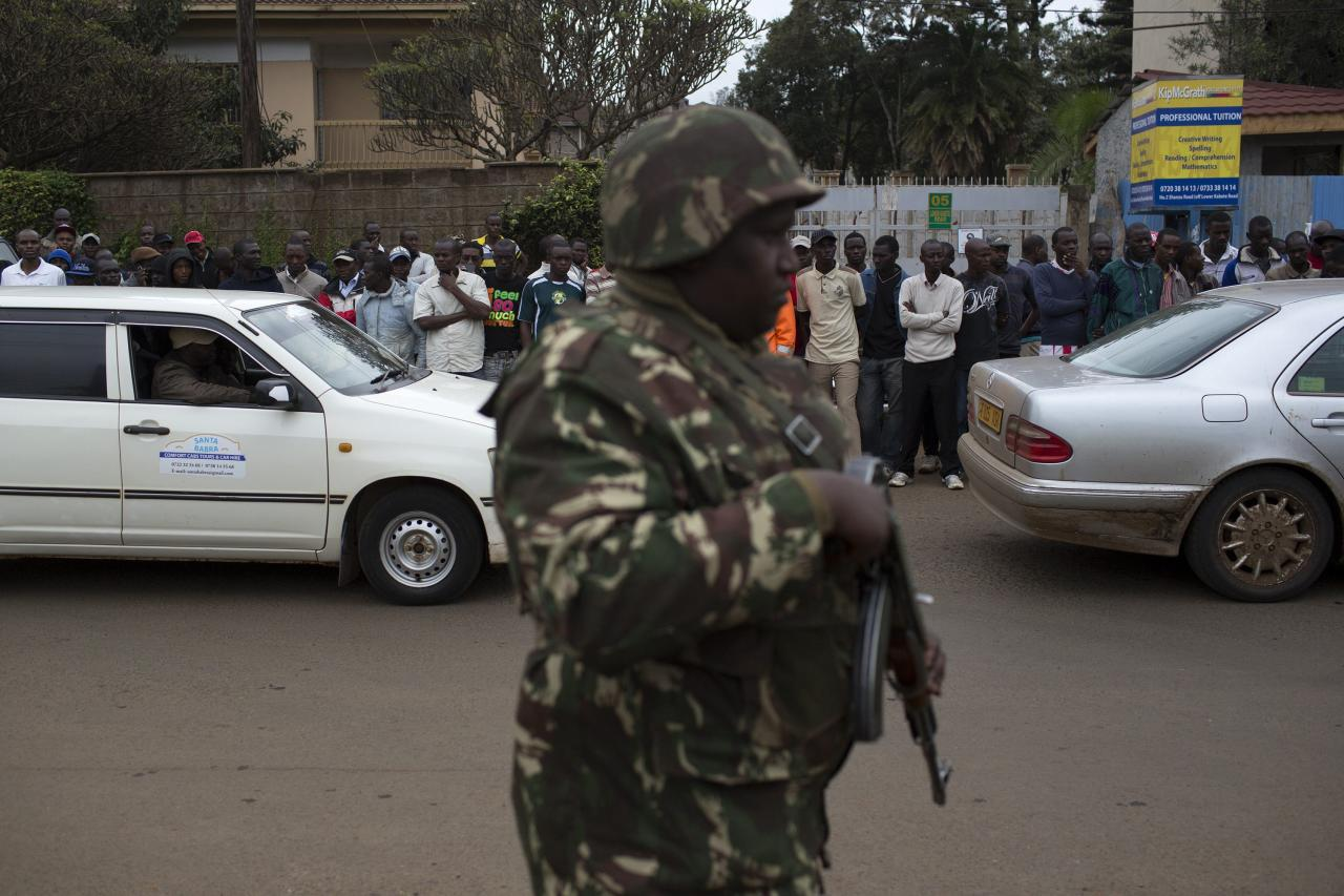 A soldier patrols as onlookers watch from a distance the security operation at the Westgate Shopping Centre, where gunmen are holding hostages, in Nairobi September 22, 2013. Islamist militants were holed up with hostages on Sunday at the shopping mall in Nairobi, where at least 59 people have been killed in an attack by the al Shabaab group that opposes Kenya's participation in a peacekeeping mission in neighbouring Somalia. A volley of gunfire lasting about 30 seconds interrupted a stalemate of several hours, a Reuters witness said, speaking from near the Westgate shopping centre that has several Israeli-owned outlets and is frequented by expatriates and Kenyans. REUTERS/Siegfried Modola (KENYA - Tags: CIVIL UNREST MILITARY)