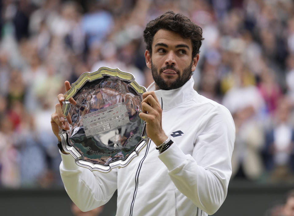 Italy's Matteo Berrettini holds up his runner-up plate for the photographers after he was defeated by Serbia's Novak Djokovic in the men's singles final on day thirteen of the Wimbledon Tennis Championships in London, Sunday, July 11, 2021. (AP Photo/Kirsty Wigglesworth)