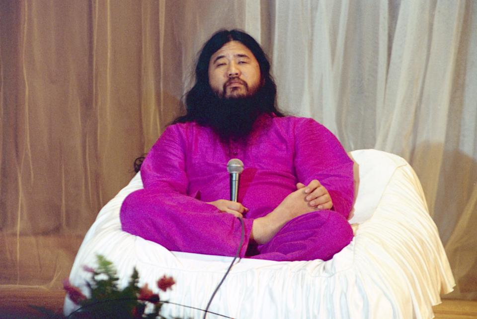 Shoko Asahara, leader of the cult group Aum Shinrikyo, wearing pink robes and sitting cross-legged on stage during his visit to Moscow, Russia, on 17th February 1994.   (Photo by Wojtek Laski/Getty Images)