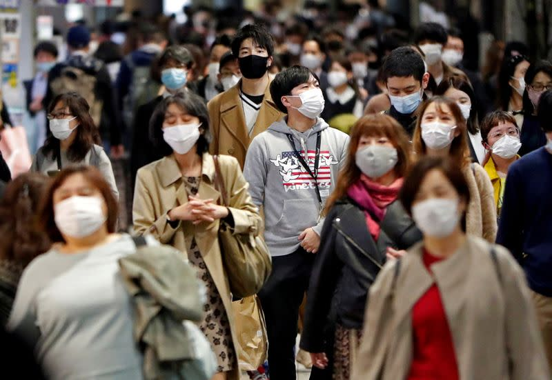 FILE PHOTO: People wearing protective face masks walk on the street, amid the coronavirus disease (COVID-19) outbreak, in Tokyo, Japan