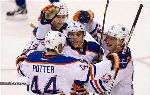 Edmonton Oilers' Taylor Hall, centre, celebrates his game-tying goal against the Vancouver Canucks with teammates Corey Potter, 44, Jordan Eberle, 14, and Ales Hemsky, of the Czech Republic, during the third period of an NHL hockey game in Vancouver, British Columbia on Tuesday Jan. 24, 2012. (AP Photo/The Canadian Press, Darryl Dyck)