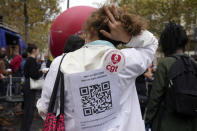 """A medical worker wearing a paper reading """"No to QR code, No to Health Pass , the vaccin does not prevent for the virus transmission, Freedom to choose to be vaccinated"""" during a protest gathering outside the Health Ministry in Paris, Tuesday, Sept. 14, 2021 against a law requiring them to get vaccinated by Wednesday or risk suspension from their jobs. The law is aimed at protecting patients from new surges of COVID-19. Most of the French population is vaccinated but a vocal minority are against the vaccine mandate. (AP Photo/Francois Mori)"""
