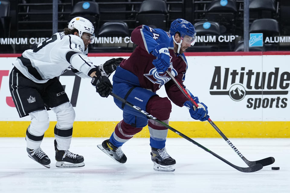 Colorado Avalanche defenseman Patrik Nemeth (24) moves the puck under pressure from Los Angeles Kings right wing Alex Iafallo (19) during the first period of an NHL hockey game Wednesday, May, 12, 2021, in Denver. (AP Photo/Jack Dempsey)
