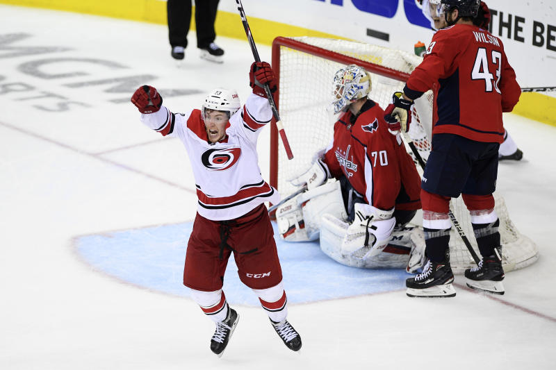 Carolina Hurricanes left wing Brock McGinn, left, celebrates his game-winning goal during double overtime of Game 7 of an NHL hockey first-round playoff series against Washington Capitals goaltender Braden Holtby (70) and right wing Tom Wilson (43), Wednesday, April 24, 2019, in Washington. The Hurricanes won 4-3 in double overtime. (AP Photo/Nick Wass)