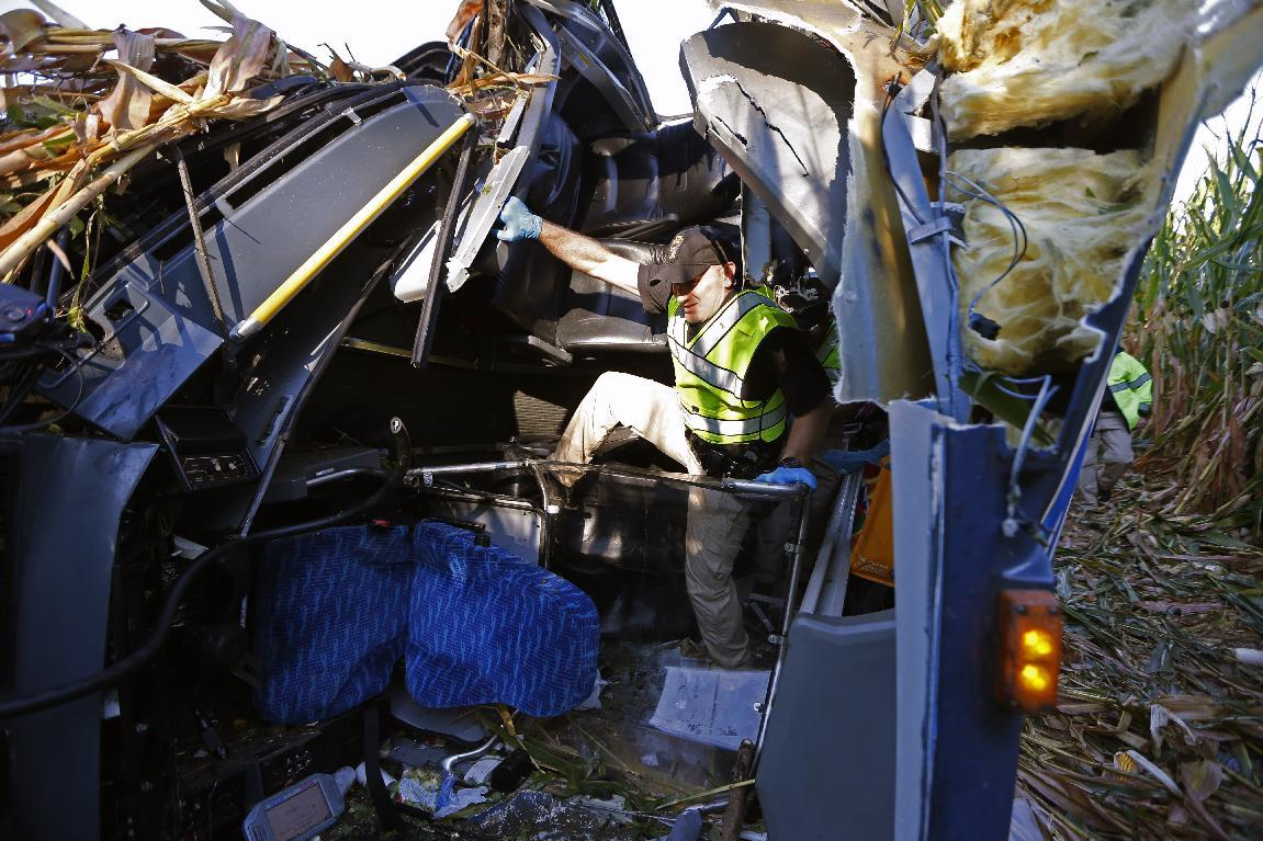 An Ohio Highway State Patrol officer investigates an overturned Greyhound bus following a crash on Saturday, Sept. 14, 2013, along interstate 75 in Liberty Township, Ohio. At least 35 people were injured in the accident. (AP Photo/The Cincinnati Enquirer, Jeff Swinger)