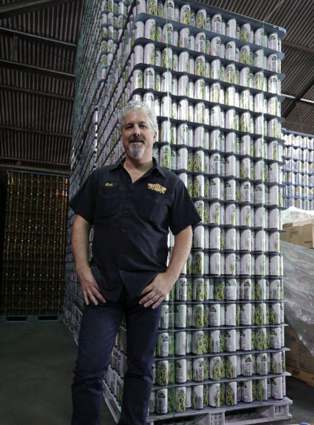 NOLA Brewing Co. LLC, CEO Kirk Coco stands in front of a stack of cans for their MechaHopzilla brand beer at the brewery in New Orleans, Tuesday, Sept. 10, 2013. The Japanese company that produced the classic Godzilla series of movies has sued the New Orleans brewery, claiming the MechaHopzilla beer brand infringes on its Mechagodzilla copyrights and trademarks. (AP Photo/Gerald Herbert)