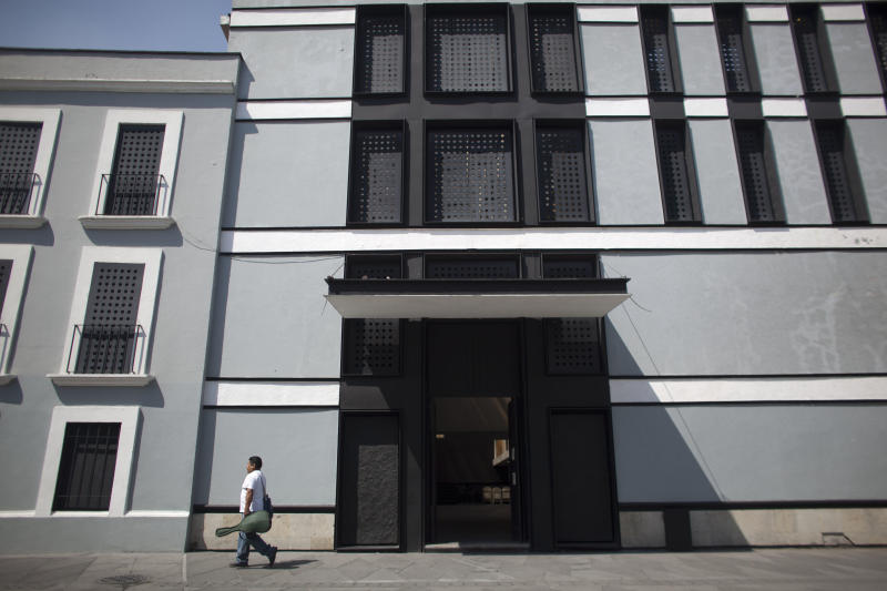 In this Oct. 22, 2012 photo, student Moises Lopez Gimenez leaves the Mariachi School Ollin Yoliztli in Mexico City. The new mariachi school in Mexico City is seeking to revive a music that's lost ground over the years. The school, whose name means life and movement in indigenous Nahautl, teaches folk bands how to play professionally while grooming a new generation of songwriters and composers. (AP Photo/Alexandre Meneghini)