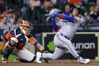 Texas Rangers' Willie Calhoun, right, loses his helmet as he strikes out swinging in front of Houston Astros catcher Martin Maldonado, left, during the fifth inning of a baseball game Friday, May 14, 2021, in Houston. (AP Photo/Michael Wyke)