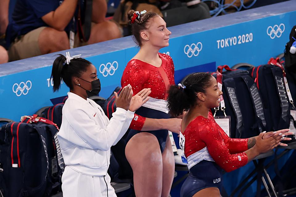 TOKYO, JAPAN - JULY 27: (L-R) Simone Biles, Grace McCallum, and Jordan Chiles cheer for Sunisa Lee of Team United States (not pictured) as she competes on uneven bars during the Women's Team Final on day four of the Tokyo 2020 Olympic Games at Ariake Gymnastics Centre on July 27, 2021 in Tokyo, Japan. (Photo by Jamie Squire/Getty Images)
