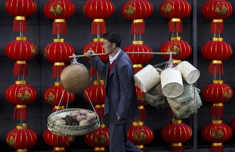 A basket vendor walks past red lanterns serving as decorations to celebrate the new year outside a shopping mall in Kunming