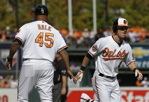 Baltimore Orioles' Nate McLouth, right, high-fives third base coach DeMarlo Hale as he rounds the bases after hitting a solo home run in the first inning of a baseball game in Baltimore, Sunday, Sept. 30, 2012. (AP Photo/Patrick Semansky)