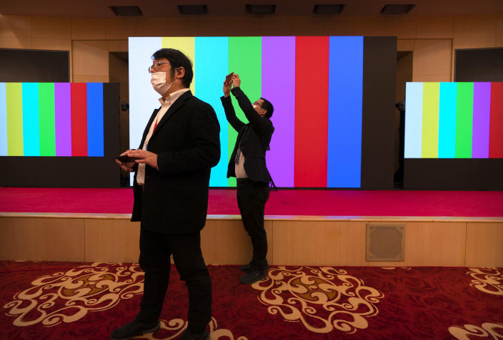 Staff members take smartphone photos before a remote video press conference by Chinese Foreign Minister Wang Yi held on the sidelines of the annual meeting of China's National People's Congress (NPC) in Beijing, Sunday, March 7, 2021. (AP Photo/Mark Schiefelbein)