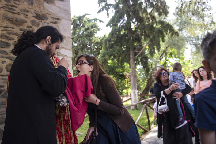 In this Sunday, May 24, 2020, photo, a Greek Orthodox priest uses a shared spoon to distribute Holy Communion during Sunday Mass in the northern city of Thessaloniki, Greece. Contrary to science, the Greek Orthodox Church and its followers insist it is impossible for disease, including the coronavirus, to be transmitted through Holy Communion. (AP Photo/Giannis Papanikos)